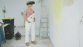 Kvinnlig målare som tycker om virtuell verklighethörlurar med mikrofon arkivfilmer