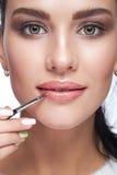 Kvinnlig målarfärg hennes kanter vid kosmetisk borsteläppstift på kanter Fotografering för Bildbyråer