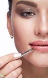 Kvinnlig målarfärg hennes kanter vid kosmetisk borsteläppstift på kanter Royaltyfri Bild