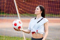 Kvinnlig målvaktboll i hans händer som står på fotbollmålet arkivbild
