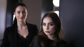 Kvinnlig makeupkonstnär med ett mörkt hår och en ung ladyt som ser spegeln och beundrar makeupjobbet i en skönhet arkivfilmer
