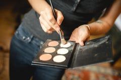 Kvinnlig makeupkonstnär med skönhetsmedel på arbete Fotografering för Bildbyråer