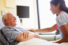 Kvinnlig man för doktor Talking To Senior i sjukhusrum royaltyfria foton