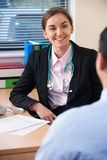 Kvinnlig manlig patient för doktor Having Discussion With i kirurgi Arkivbilder