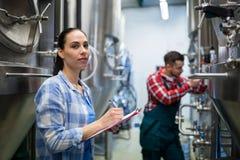Kvinnlig maskin för bryggeri för underhållsarbetarprovning royaltyfri fotografi