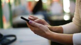 Kvinnlig maskinskrivning på en telefon arkivfilmer