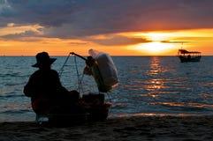 Kvinnlig matförsäljare på den Otres stranden under solnedgång royaltyfri fotografi