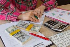 Kvinnlig med affärsplan, räknemaskinen, dollarsedeln, spreadshee och pennan på tabellen Arkivbilder