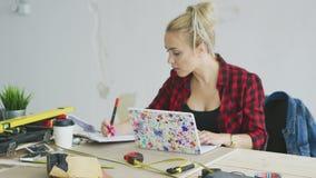Kvinnlig med bärbar datorhandstil i anteckningsbok arkivfilmer