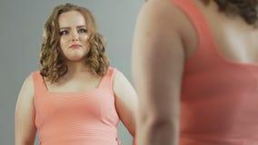 Kvinnlig med extra vikt som ser hennes reflexion i spegel med själv-avsky stock video