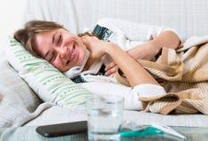 Kvinnlig med hemmastadd feber Arkivbild