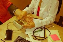 Kvinnlig medicindoktor som mäter blodtryck till patienten, medan prata henne Kvinnan meddelar med läkaren under medicinsk exa fotografering för bildbyråer