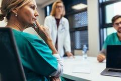 Kvinnlig medicinsk professionell i personalmöte arkivbild