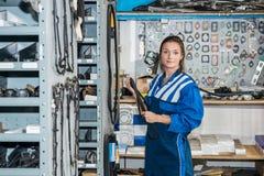 Kvinnlig mekaniker Holding Timing Belt i lager av garaget arkivfoto