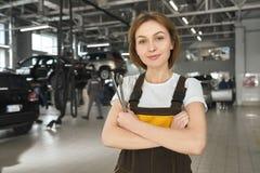 Kvinnlig mekaniker med skiftnycklar som poserar i autoservice royaltyfria bilder