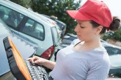 Kvinnlig mekaniker som är klar till det chane gummihjulet med hjulskiftnyckeln royaltyfri bild