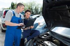 Kvinnlig mekaniker som arbetar på bilmotorn med kollegan royaltyfria bilder
