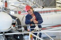 Kvinnlig mekaniker som arbetar på flygplan royaltyfri bild