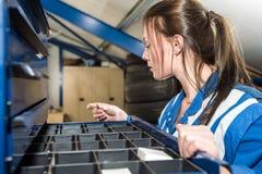 Kvinnlig mekanikerSelecting Screw From enhet på garaget arkivfoto