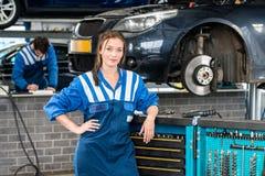 Kvinnlig mekanikerStanding By Tool spårvagn i garage Royaltyfria Foton