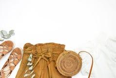 Kvinnlig modebakgrund Stilfull moderiktig kvinnlig sommarkläduppsättning Kortslutningar vitt omslag, sandaler, rund rottingpåse,  arkivbild