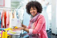 Kvinnlig modeformgivare som använder symaskinen Arkivfoton