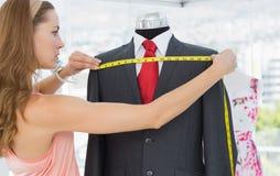 Kvinnlig modeformgivare som mäter dräkten på attrapp Royaltyfria Bilder