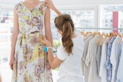 Kvinnlig modeformgivare som mäter modellen Arkivbild