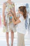 Kvinnlig modeformgivare som mäter modellmidjan Royaltyfri Bild