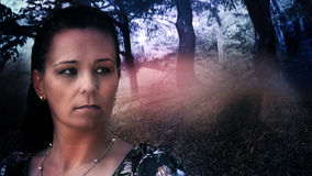 Kvinnlig modell, bakgrund med den mystiska mörka skogen Arkivbild