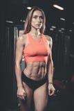 Kvinnlig modell för Caucasian sexig kondition i idrottshallslut upp abs Arkivbild