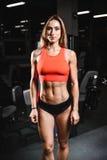 Kvinnlig modell för Caucasian sexig kondition i idrottshallslut upp abs Fotografering för Bildbyråer