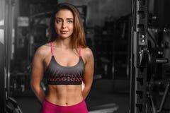 Kvinnlig modell för Caucasian sexig kondition i idrottshallslut upp abs Arkivfoton