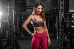 Kvinnlig modell för Caucasian sexig kondition i idrottshallslut upp abs Arkivfoto
