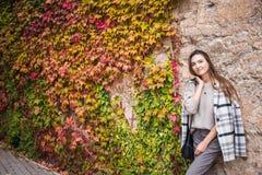 Kvinnlig modell i moderiktig dräkt på steetväggbakgrunden arkivfoton