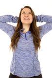 Kvinnlig modell med hennes armar bak hennes huvud som sträcker att le Arkivfoto