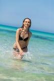Kvinnlig modell som bär den svarta bikinin i vattnet arkivbilder
