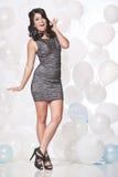 Kvinnlig modemodell som poserar med en ballongbakgrund med en gyckel Arkivbild