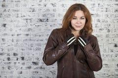 Kvinnlig motorcyklist för långt hår som av tar hennes bruna läderomslag, bakgrund för tegelstenvägg, copyspace Arkivbild