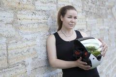 Kvinnlig motorcyklist som poserar med den vita hjälmen nära stenväggar, kopieringsutrymme Fotografering för Bildbyråer