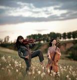 Kvinnlig musikalisk duett med fiolen och violoncellen spelar på äng royaltyfri foto