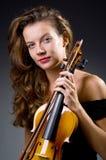 Kvinnlig musikalisk spelare mot mörk bakgrund Arkivfoto