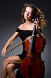 Kvinnlig musikalisk spelare mot mörk bakgrund Arkivfoton