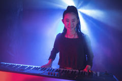 Kvinnlig musiker som spelar pianot i upplyst nattklubb Royaltyfria Foton