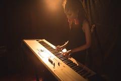 Kvinnlig musiker som spelar pianot i upplyst nattklubb Arkivbild
