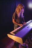 Kvinnlig musiker som spelar pianot i upplyst nattklubb Arkivfoto