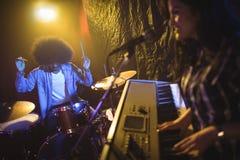 Kvinnlig musiker som spelar pianot med handelsresanden i nattklubb Royaltyfria Bilder