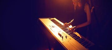 Kvinnlig musiker som spelar pianotangentbordet i upplyst klubba Royaltyfri Bild