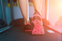 Kvinnlig muskulös fot i gymnastikskor som kör på trampkvarnen på idrottshallen Royaltyfri Foto