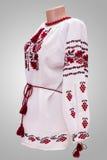 Kvinnlig nationell folklore för skjorta, en folk dräkt Ukraina, på bakgrund för grå vit Arkivfoto